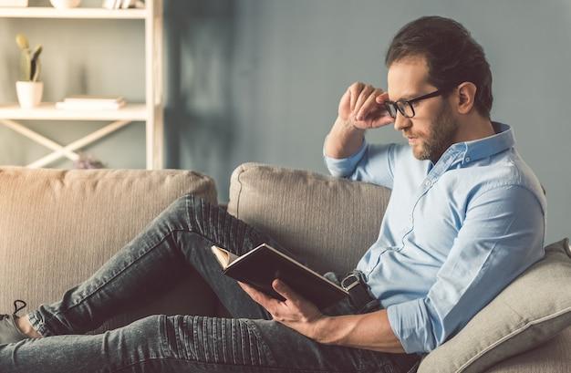 L'uomo d'affari bello in occhiali sta leggendo un libro.
