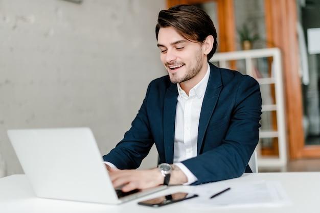 L'uomo d'affari bello in un vestito utilizza il computer portatile nell'ufficio
