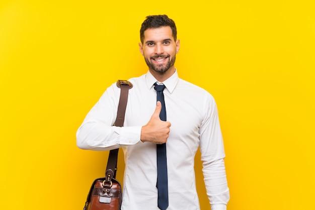 L'uomo d'affari bello sopra la parete gialla isolata che dà pollici aumenta il gesto