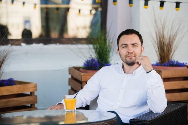 L'uomo d'affari bello sta aspettando il cliente nel self-service. tocca l'orologio e lo guarda con anticipazione. l'uomo è seduto a tavola all'aperto e sorride.
