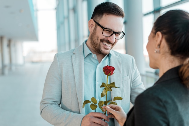L'uomo d'affari che dà è aumentato al collega femminile nel corridoio dell'ufficio.