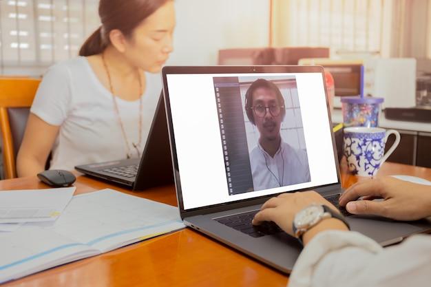 L'uomo d'affari che fa la videoconferenza facendo uso del lavoro del computer portatile dalla casa impedisce il concetto covid-19.