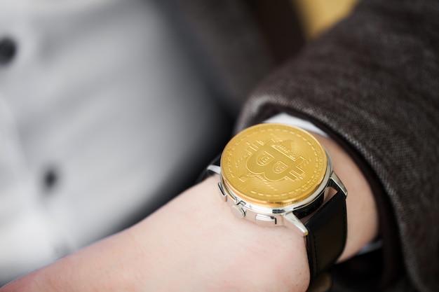 L'uomo d'affari che investe nella valuta cripto bitcoin e nell'etere, tiene nelle mani di un orologio della sabbia