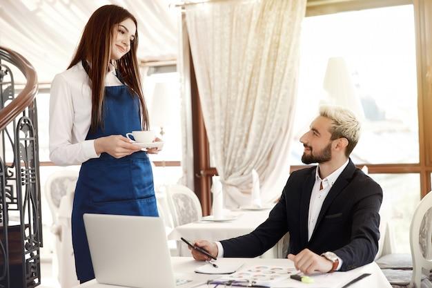 L'uomo d'affari che lavora sta ordinando qualcosa al ristorante e una bella cameriera sta servendo un caffè