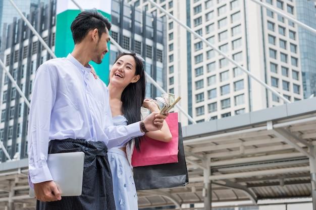 L'uomo d'affari che tiene i contanti del dollaro con il computer portatile e la borsa della spesa asiatica della tenuta della donna è sorridere felice nell'ambiente urbano