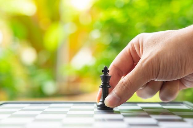 L'uomo d'affari che tiene un re chess è disposto su una scacchiera.