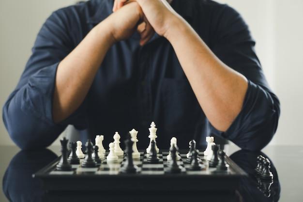 L'uomo d'affari che tiene un re scacchi è disposto su una scacchiera