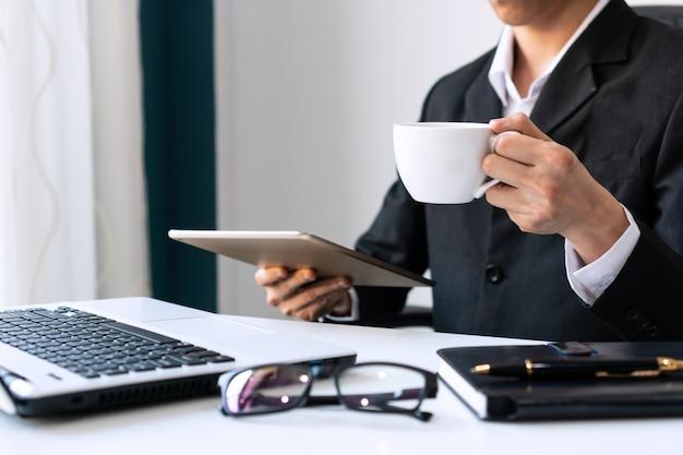 L'uomo d'affari che tiene una tazza di caffè bianco e beve il caffè di mattina mentre tiene la compressa.