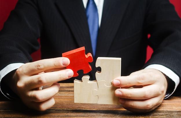 L'uomo d'affari collega un puzzle rosso all'assemblea