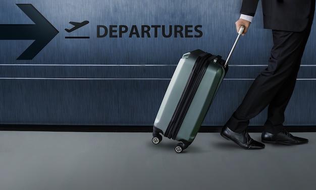 L'uomo d'affari con i bagagli cammina dentro il terminale di partenze dell'aeroporto