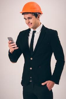 L'uomo d'affari con il casco protettivo sta usando uno smartphone