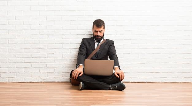 L'uomo d'affari con il suo portatile seduto sul pavimento è un po 'nervoso e spaventato mentre preme i denti