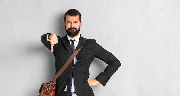 L'uomo d'affari con la barba che mostra il pollice giù firma con l'espressione negativa