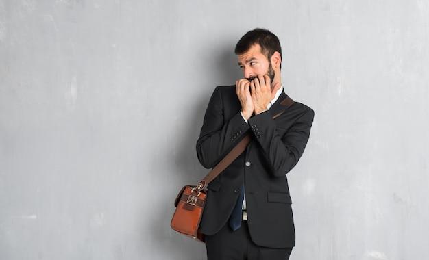 L'uomo d'affari con la barba è un po 'nervoso e spaventato mettendo le mani in bocca