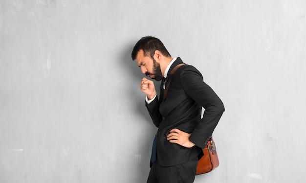 L'uomo d'affari con la barba soffre di tosse e si sente male