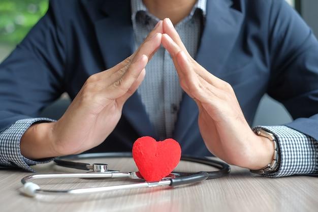 L'uomo d'affari consegna il cuore e lo stetoscopio. sanità e assicurazione