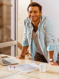 L'uomo d'affari del mulatto sta sorridendo mentre lavorava nell'ufficio.