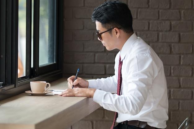 L'uomo d'affari dell'asia non fesh, sonnolenta e sbadigliante, sfondo caffetteria