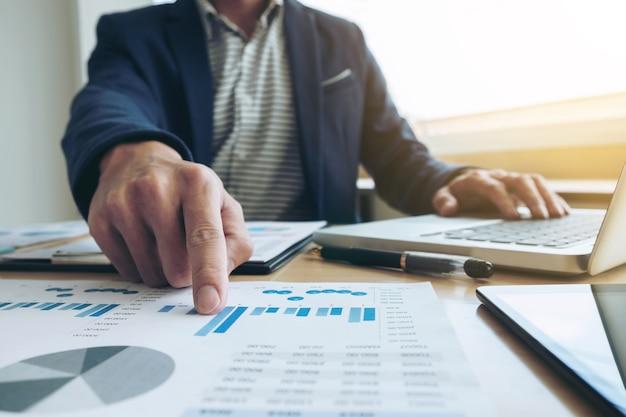 L'uomo d'affari della mano che lavora e che punta al progetto di finanza del documento grafico