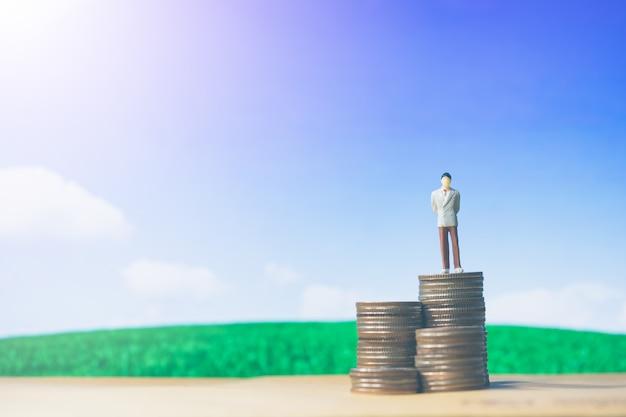 L'uomo d'affari delle piccole figure della gente miniatura sta su soldi