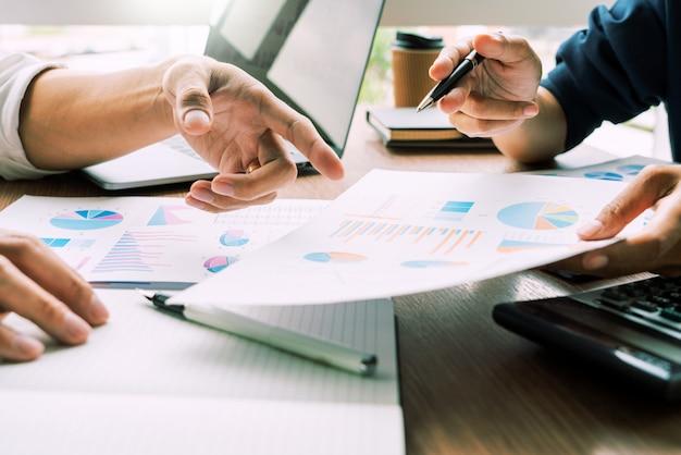 L'uomo d'affari discute spiegando le nuove informazioni di tendenze su un documento con il collega o il collega del collega insieme in un ufficio moderno di affari.