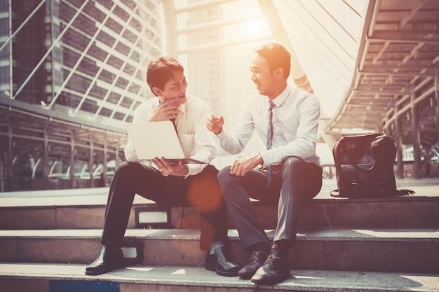L'uomo d'affari due sta lavorando con lo smart phone ed il taccuino per il concetto di affari.