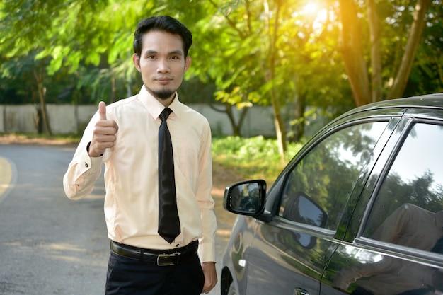 L'uomo d'affari e l'automobile hanno parcheggiato sulla via, concetto di vendita di assicurazione