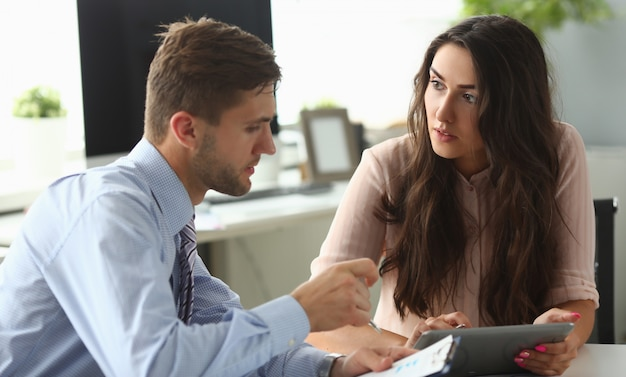 L'uomo d'affari e la donna di affari conferiscono in ufficio