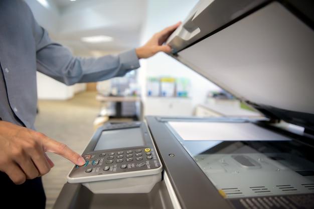 L'uomo d'affari è pulsante sul pannello della stampante, fotocopiatrice.