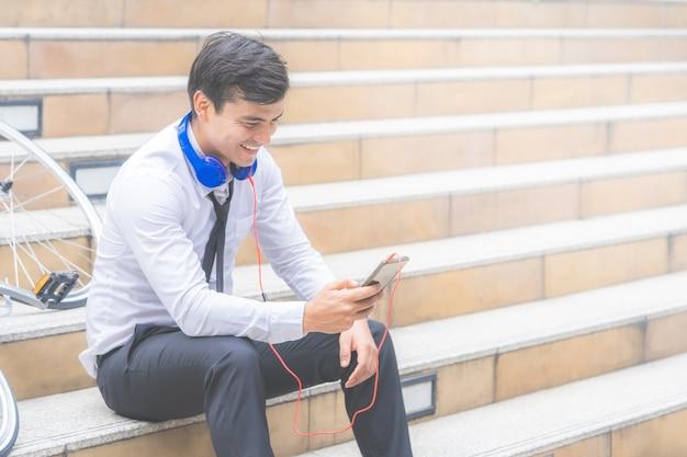 L'uomo d'affari è rilassante ascoltando musica con la sua bicicletta sul lato