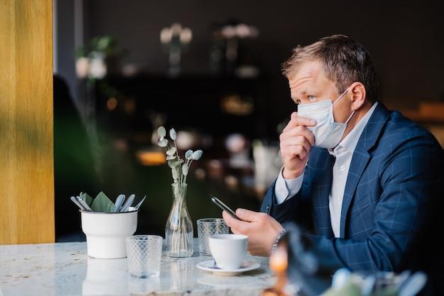 L'uomo d'affari elegante tossisce e indossa la maschera medica protettiva durante la situazione epidemica, si siede nell'accogliente caffetteria