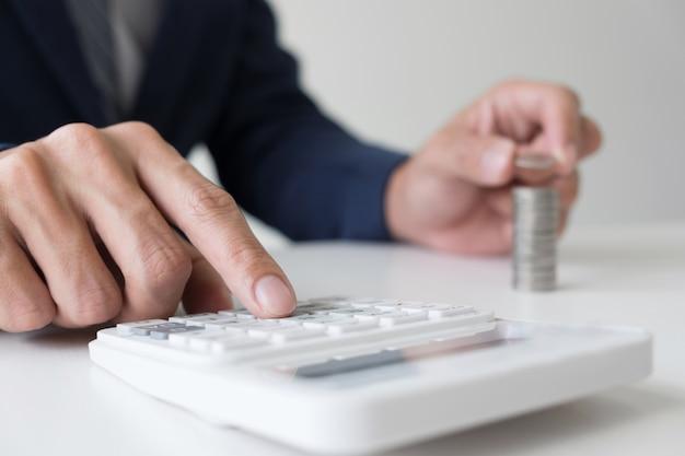 L'uomo d'affari facendo uso del calcolatore ad investimento aziendale di analisi ed impilando le monete ha organizzato a