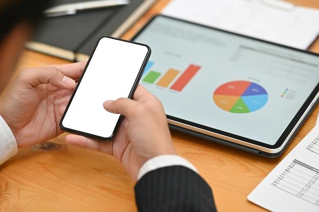 L'uomo d'affari facendo uso dello smartphone del modello con lo schermo vuoto e l'analisi digitale della compressa finanziano i dati.