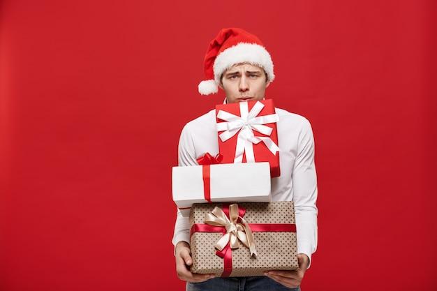 L'uomo d'affari felice caucasico bello che tiene molti regali con il cappello di santa di usura che posa su bianco ha isolato il fondo.