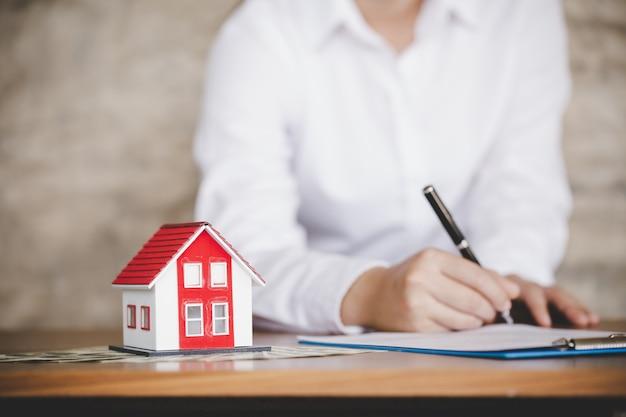 L'uomo d'affari firma il contratto dietro il modello architettonico domestico