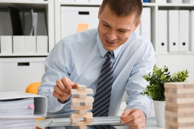 L'uomo d'affari gioca in una strategia della mano di jenga