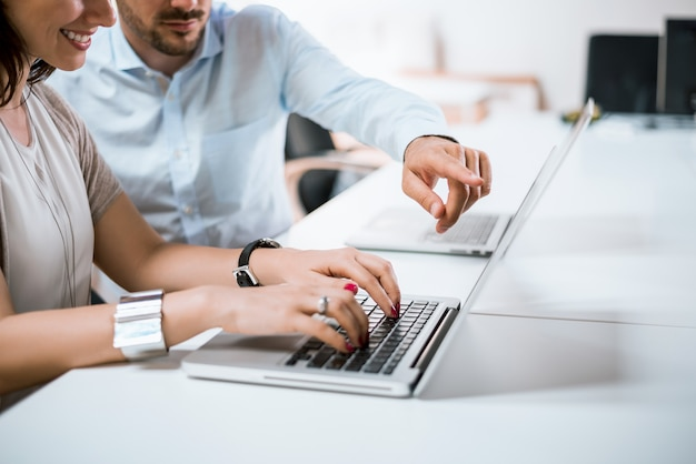 L'uomo d'affari ha indicato un dito al taccuino, capo che indica sull'annuncio divertente sul computer.