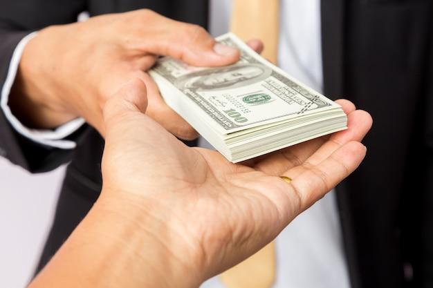 L'uomo d'affari in completo dà a un uomo i dollari americani