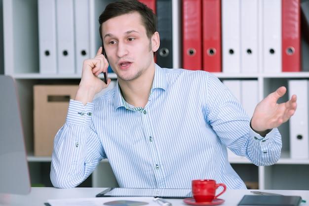 L'uomo d'affari in ufficio che parla sul telefono risolve il problema