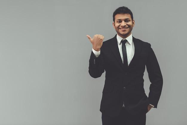 L'uomo d'affari in vestito classico sta indicando via.