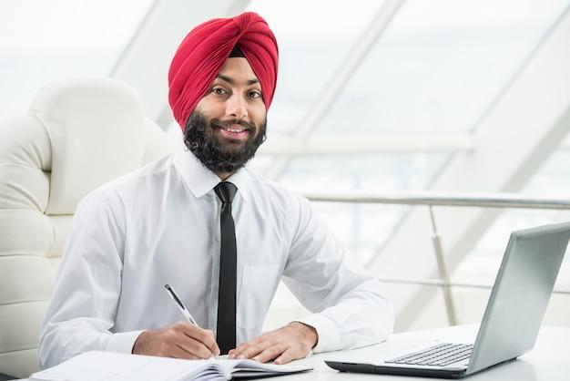 L'uomo d'affari indiano sta lavorando al suo computer nell'ufficio.