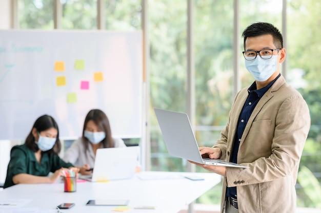 L'uomo d'affari indossa la maschera di protezione che sta e che tiene il computer portatile con sicuro