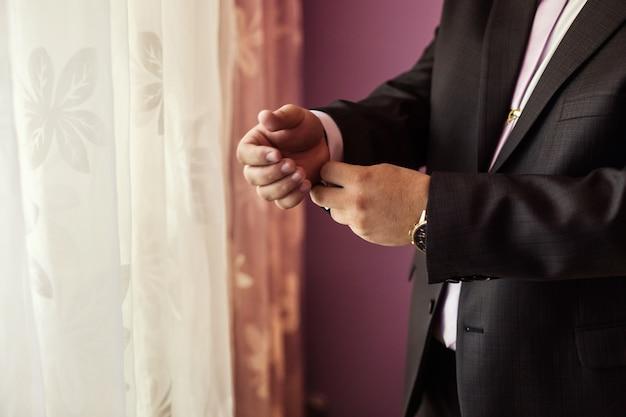 L'uomo d'affari indossa una giacca. politico, stile dell'uomo, primo piano delle mani maschile, americano, uomo d'affari europeo, affari, moda e concetto di abbigliamento