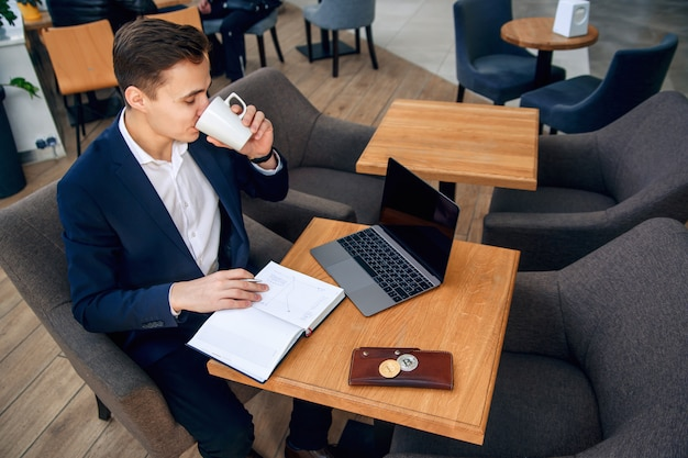 L'uomo d'affari lavora nel suo posto di lavoro con il taccuino, il computer portatile e fa un business plan