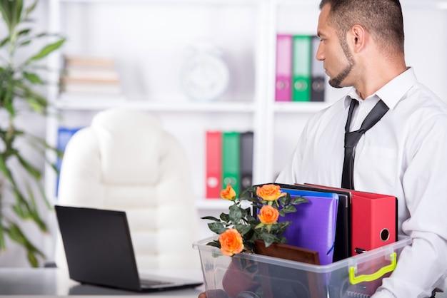L'uomo d'affari licenziato sta facendo i bagagli e sta lasciando l'ufficio.