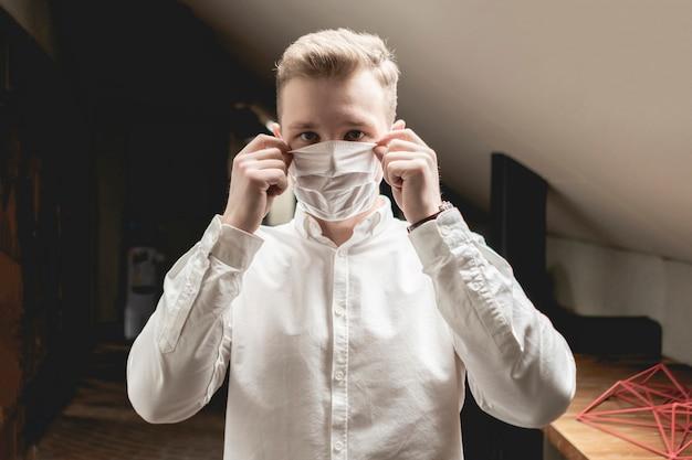 L'uomo d'affari malato nel suo ufficio indossa la maschera protettiva. concetto di malattia
