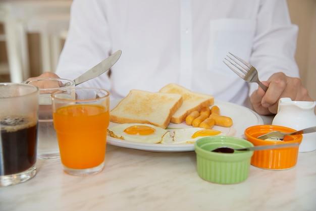 L'uomo d'affari mangia la colazione americana in un hotel