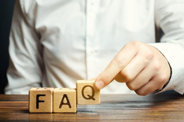 L'uomo d'affari mette i blocchi di legno con la parola faq