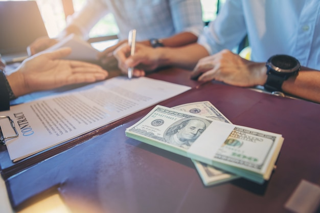 L'uomo d'affari mette la firma sul contratto alla riunione d'affari e passare i soldi.