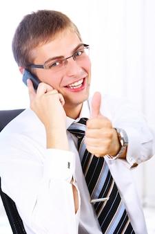 L'uomo d'affari mostra il segno giusto mentre chiama dal telefono